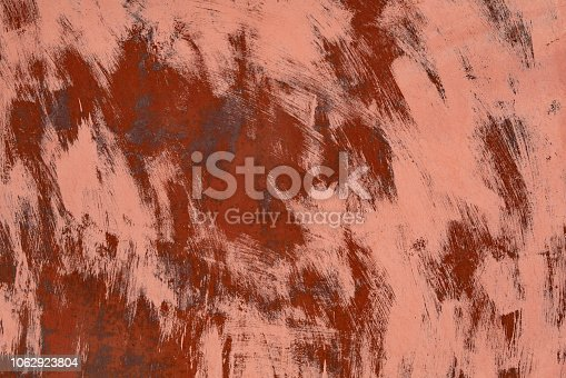 rusty metal surface painted with red color with brush strokes. close up abstract background or backdrop