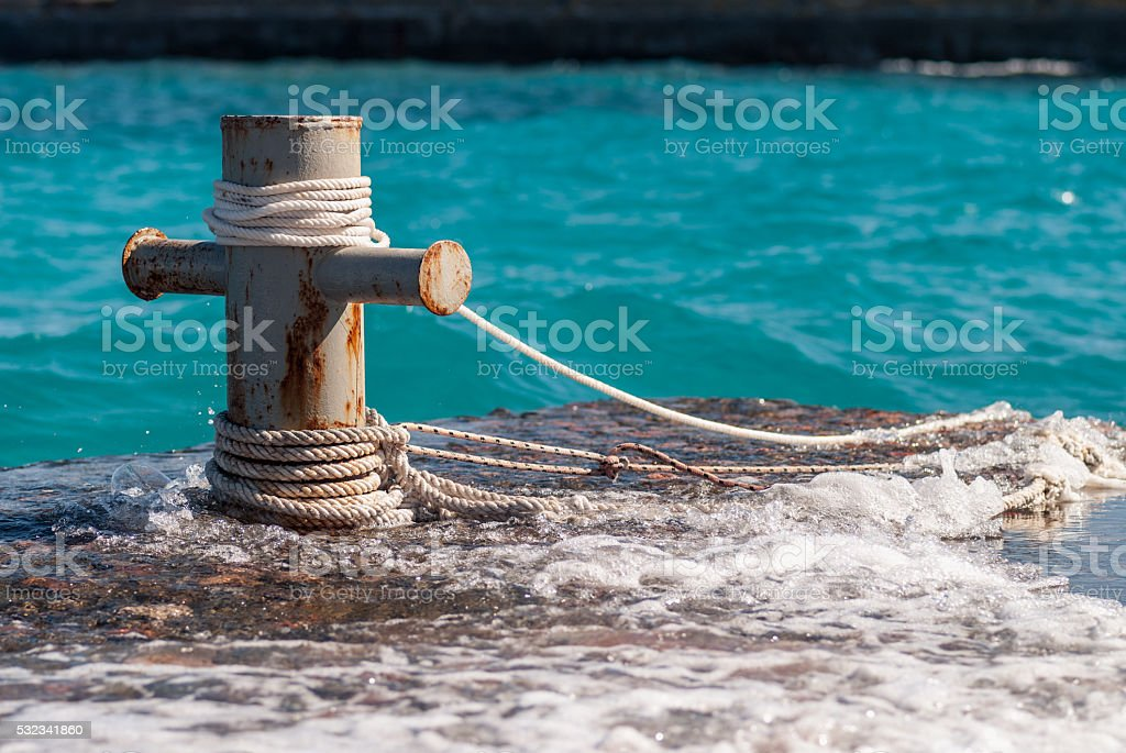 Rusty mooring bollard with ship ropes and  clear turquouse sea stock photo