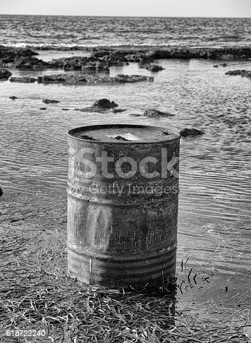 istock Rusty oil barrel near the shore of the sea 618722240