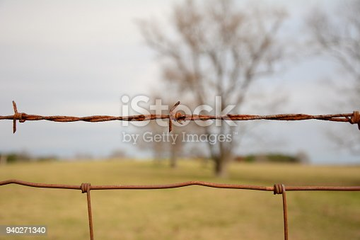 istock rusty old barbed wire fence. shallow depth of field trees for the background 940271340