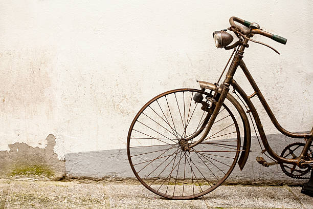 Rusty old bicycle leaning on a wall. - foto de stock