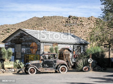 Rusty old black car at the Hackberry General Store along route 66  in Arizona during day with old garage behind