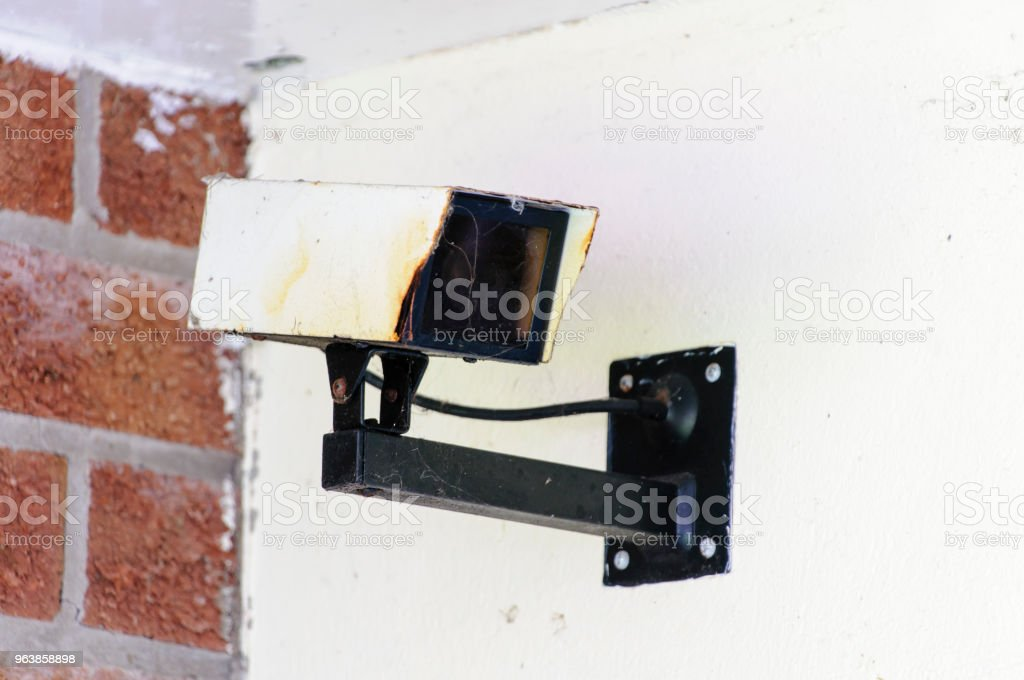 A rusty, old CCTV camera on the wall of a house - Royalty-free Appliance Stock Photo