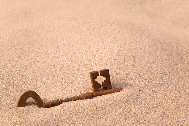 Rusty old key in sand stock photo