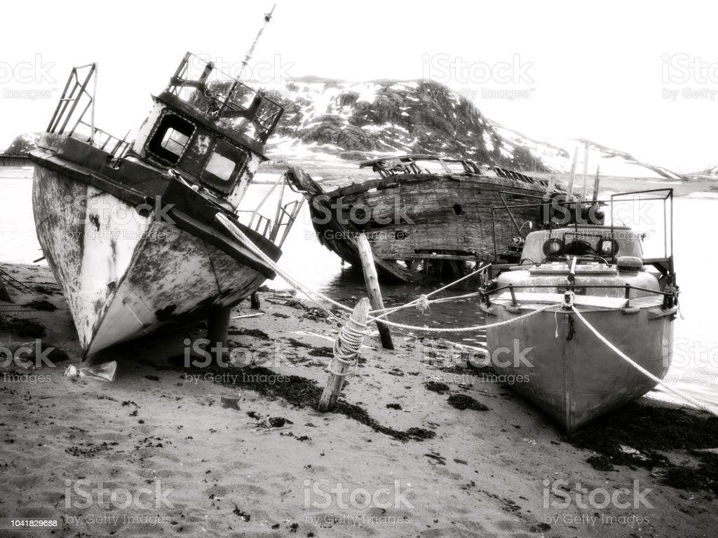 Rusty old shipwreck and boats in Teriberka stock photo