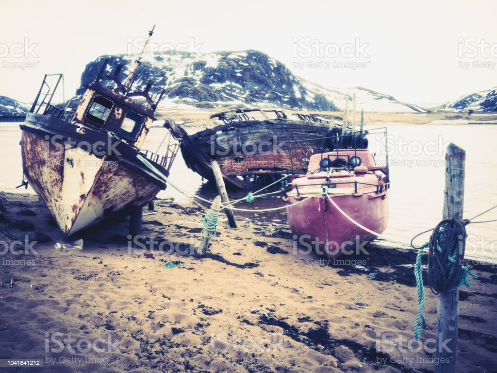 Rusty old shipwreck ruins and boats in Teriberka stock photo