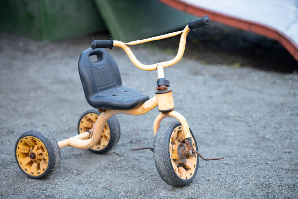 Rusty old tricycle in playground stock photo