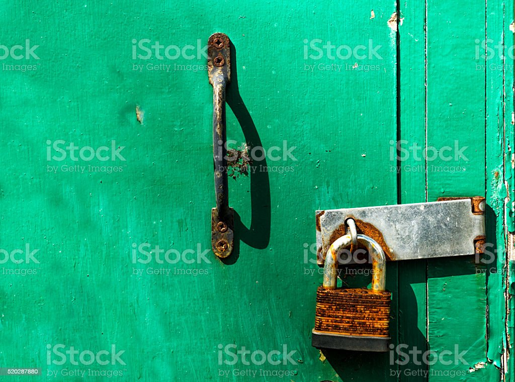 Rusty padlock on an old wooden green door with handle stock photo