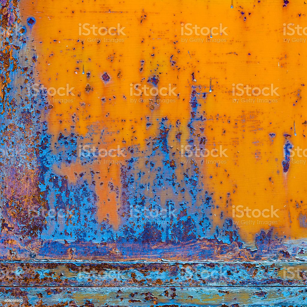 Rusty painted metal with cracked paint. Orange and blue colors stock photo