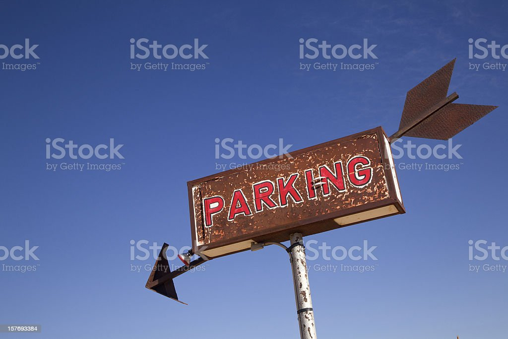 Rusty Parking Sign With Arrow Against Clear Desert Sky royalty-free stock photo
