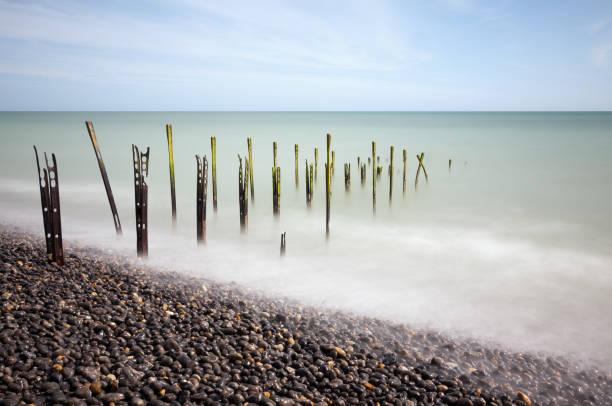 Rusty posts on beach in Sea stock photo