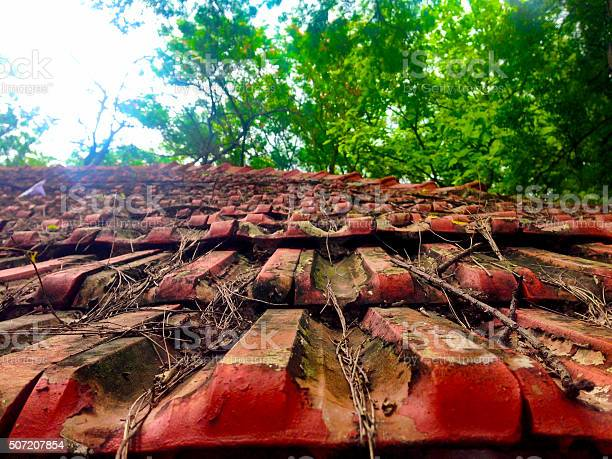 Photo of rusty red colored roof tile on the roof