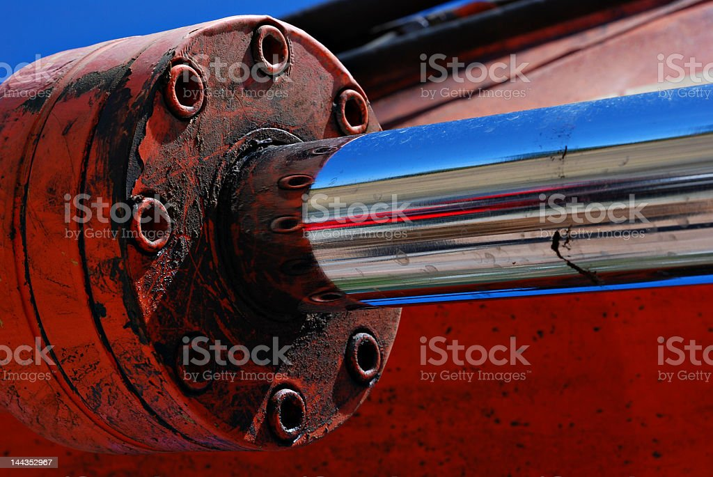 Rusty, red hydraulic arm with reflection of road and sky stock photo