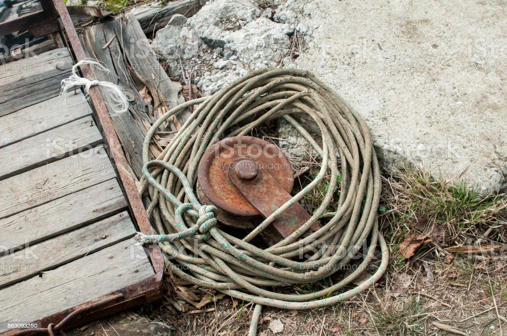 Rusty reel and weathered rope stock photo