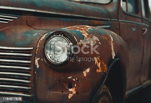 Rusty retro car with corrosion of body and cracked painting
