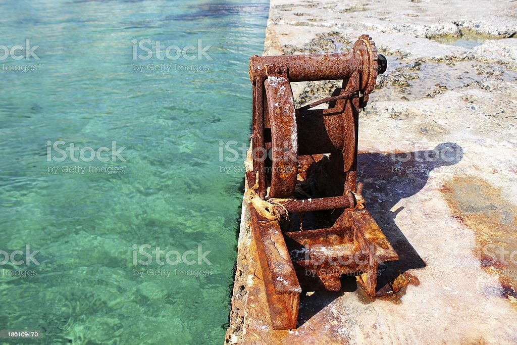 Rusty scenic metal gear and turquoise sea royalty-free stock photo
