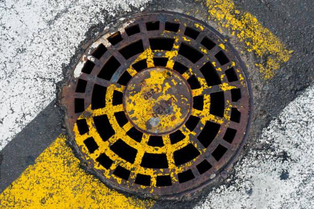 Rostige Kanalluke an einem Fußgängerüberweg. Das Konzept der alten Kommunikation, die Notwendigkeit der Reparatur. – Foto