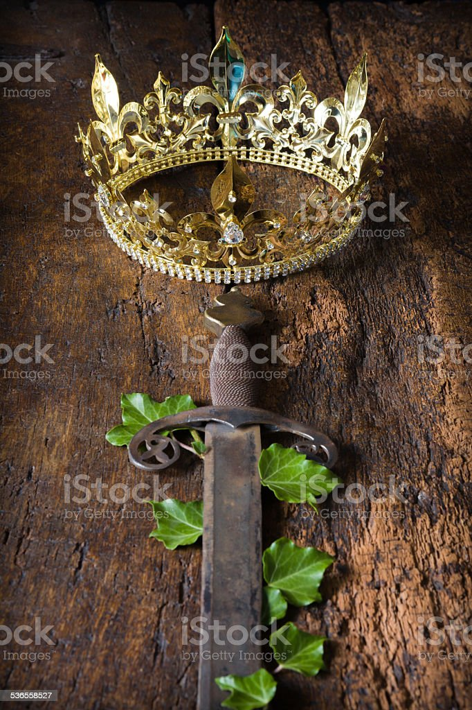 Rusty sword and golden crown stock photo