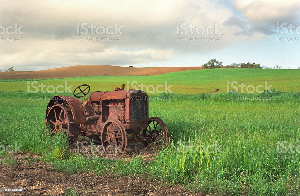 Rusty Tractor in Green Field royalty-free stock photo