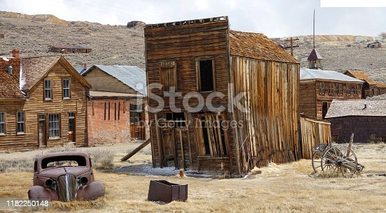 Rusty vintage car and idyllic wooden houses decay in the American wilderness after the gold rush. Scenic view of a ghost town in the Californian countryside slowly falling apart in rugged conditions.