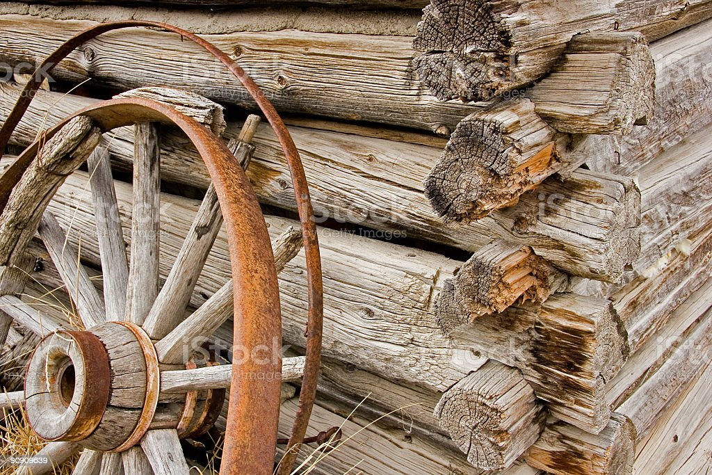 Rusty wagon wheel leaning against a wooden wall royalty-free stock photo