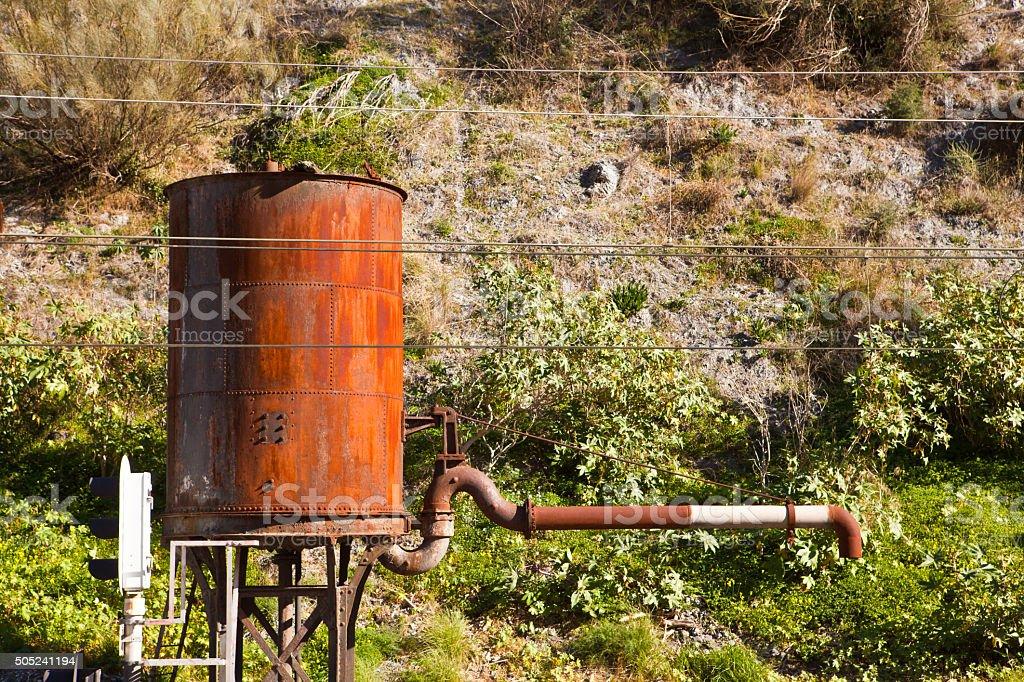 rusty water crane and tank stock photo