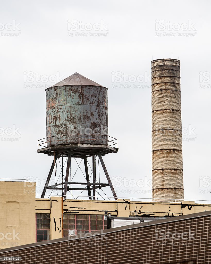 rusty water tower and smokestack vertical stock photo