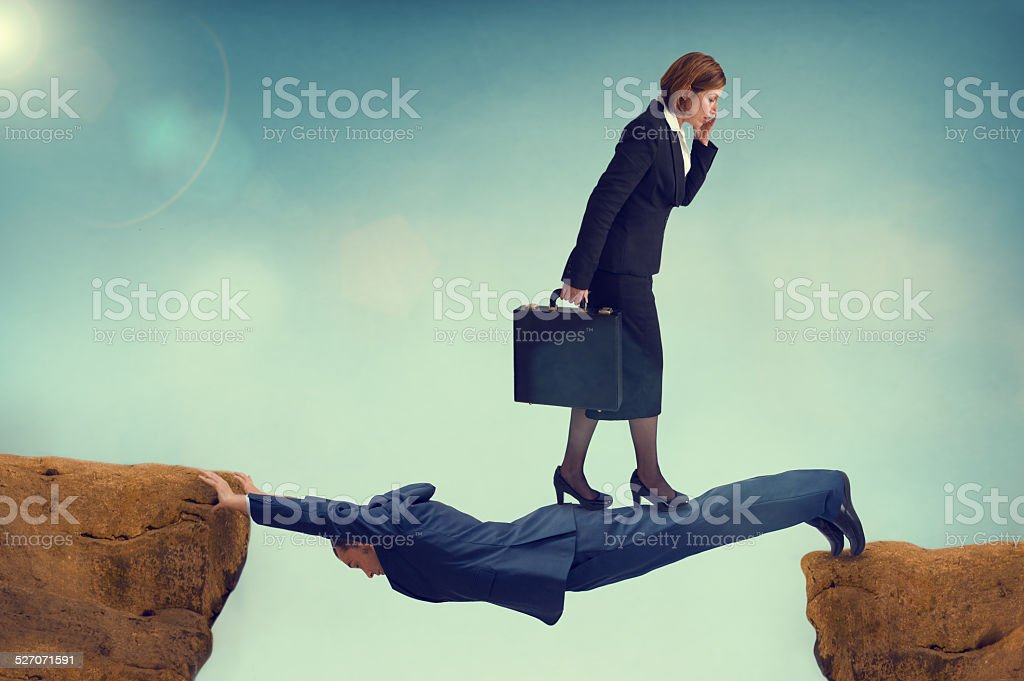ruthless business woman walking over a vulnerable businessman stock photo