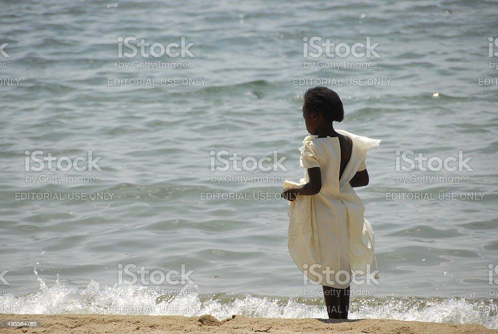 Rwandan girl stands on the Lake Kivu shore, Gisenyi, Rwanda. stock photo