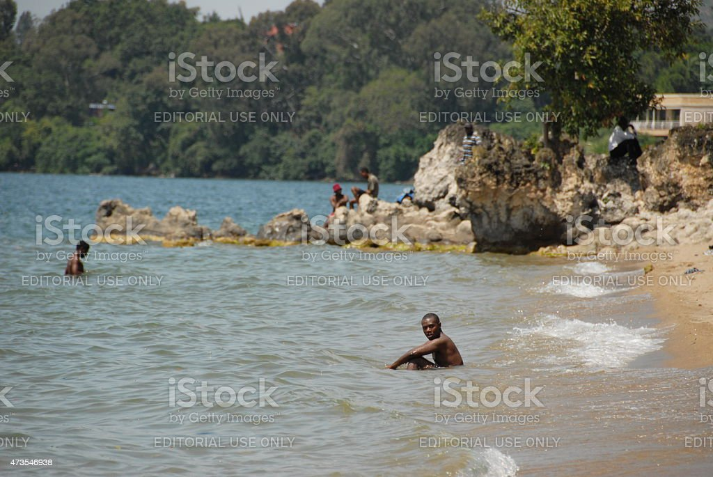 Rwandan man sits on shore of Lake Kivu, Gisenyi, Rwanda. stock photo