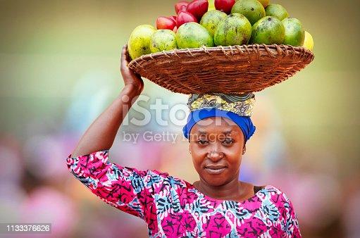 istock Rwandan woman carrying basket full of fruits 1133376626