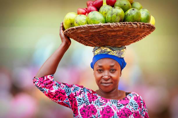 Rwandan woman carrying basket full of fruits Portrait of Rwandan woman carrying on head wicker basket full of fruits market vendor stock pictures, royalty-free photos & images