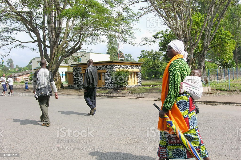 Rwandan woman walks on street with baby, Gisenyi, Rwanda. stock photo