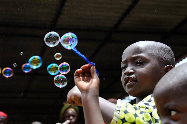 rwandese enfants jouant avec des bulles de savon - palais buccal photos et images de collection