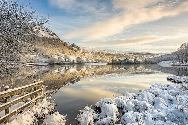 Rydal, Lake District in winter snow A beautiful still winter morning with a fresh covering of snow at Rydal Water in the Lake District UK, sunlight casting a glow upon the trees. cumbria stock pictures, royalty-free photos & images