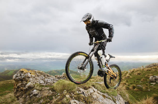 Ryder in full protective equipment on the mtb bike climbs on a rock against the backdrop of a mountain range and low clouds stock photo