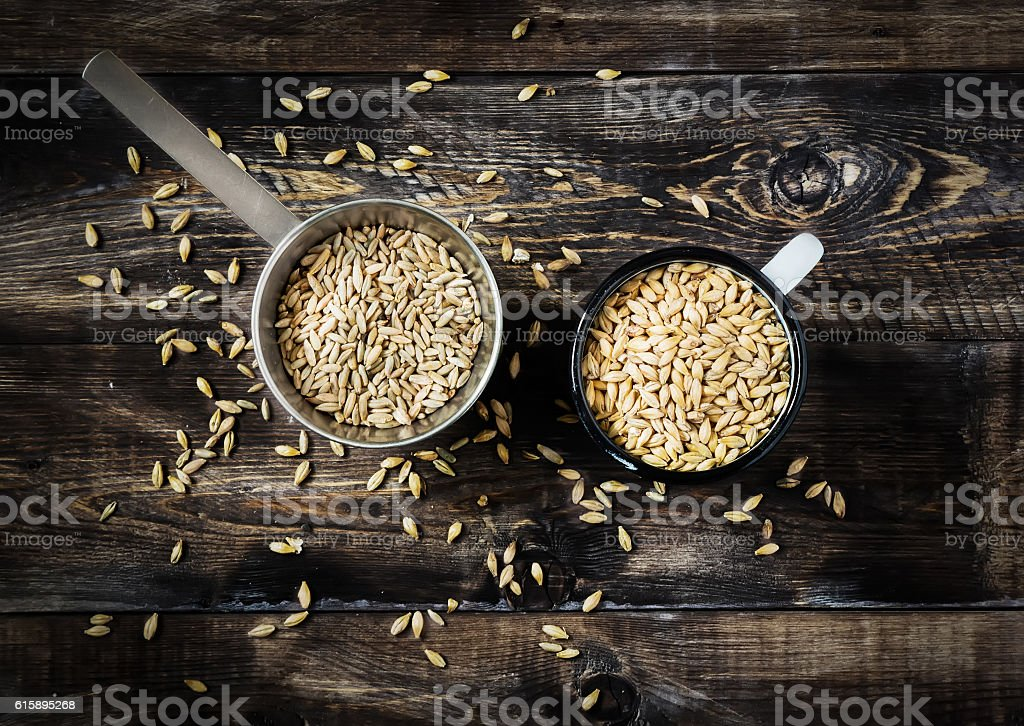 Rye and barley malt in cups on a wooden table stock photo