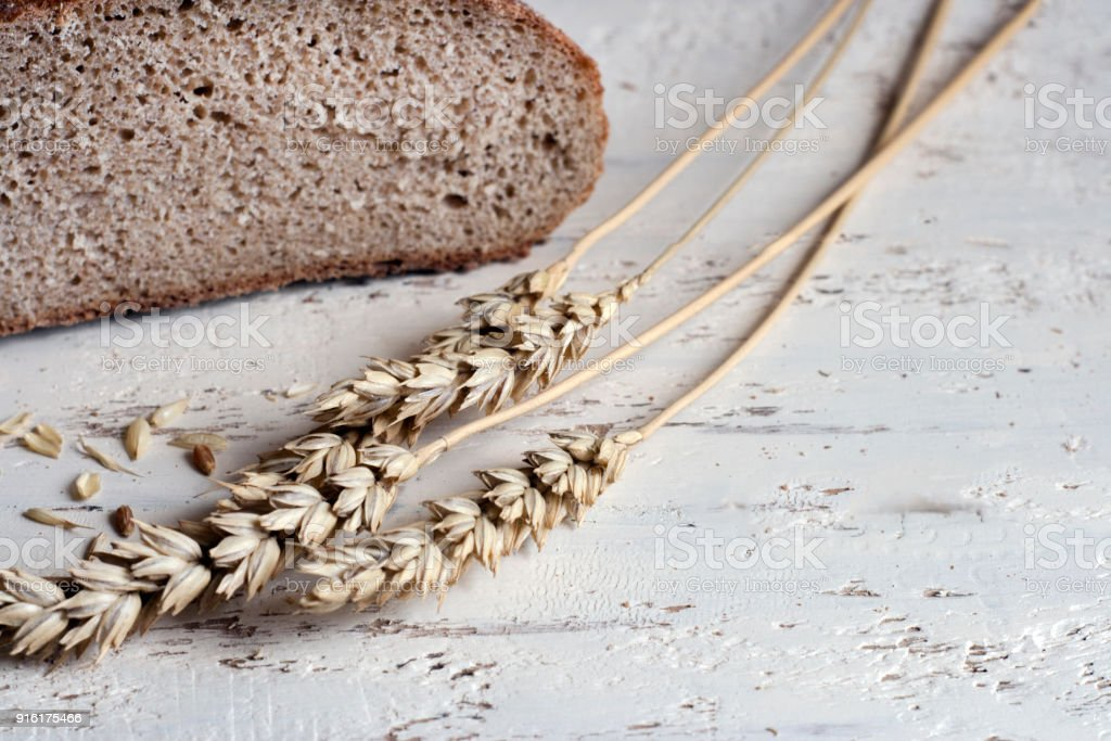 Rye bread and ears of wheat on a wooden table. Rustic Still Life stock photo