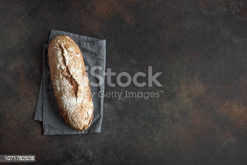 Rye bread. Fresh homemade bread on dark rustic wooden background, top view, copy space. Sourdough artisan rye bread.