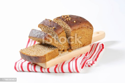 sliced rye bread with coriander seeds on wooden cutting board and striped dishtowel