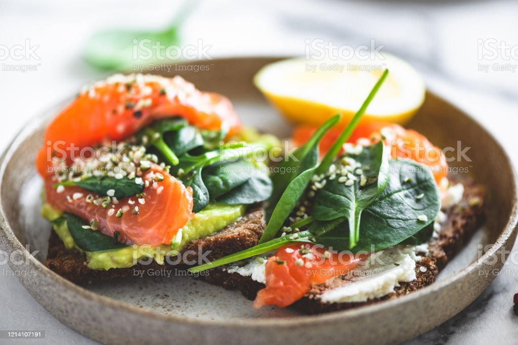 Rye bread toast with avocado, salmon, cream cheese Rye bread toast with avocado, salmon, cream cheese, spinach leaf and hemp seeds on plate. Healthy food. Appetizer, breakfast or snack Appetizer Stock Photo