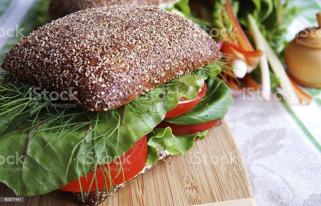 Rye bread-tomato sandwich on a wooden board royalty-free stock photo
