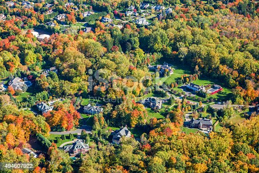 Upper middle-class suburban countryside neighborhood clad in the colors of early autumn foliage.