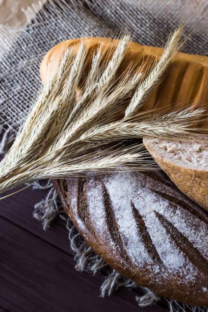 roggen, korn und weißbrot neben die ährchen roggen auf einem holztisch - mehlmotten stock-fotos und bilder