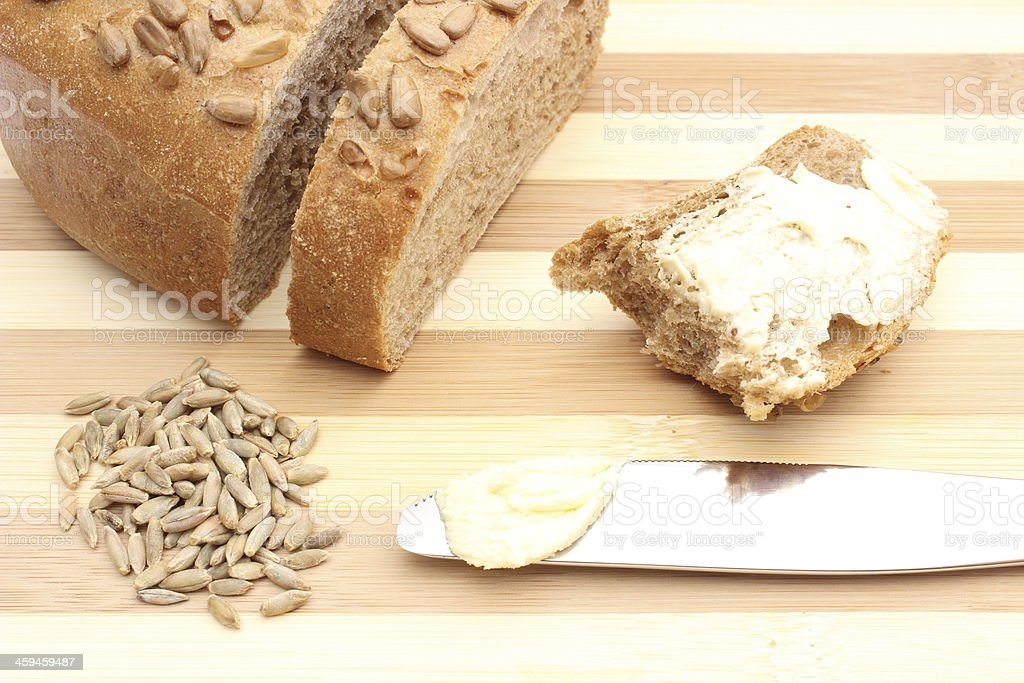 Rye grain, butter on knife and slice of bread stock photo