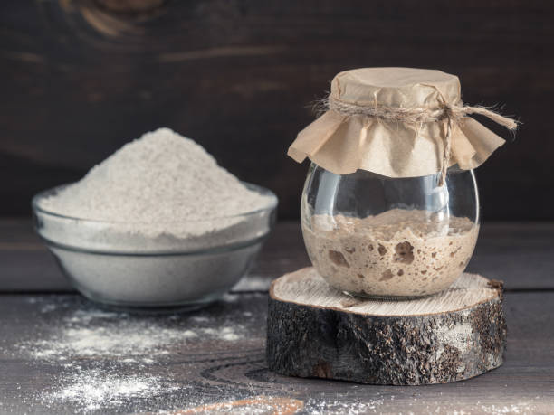 rye sourdough starter and rye flour Active rye sourdough starter in glass jar and rye flour on brown wooden background. Starter for sourdough bread. Toned image. Copy space. yeast stock pictures, royalty-free photos & images