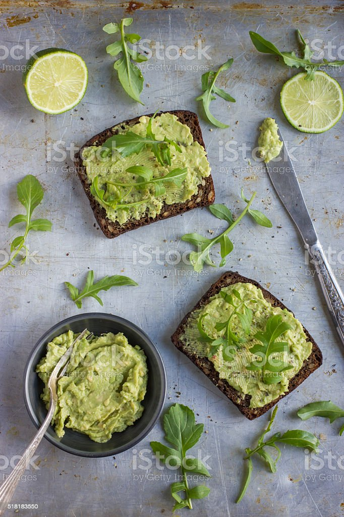 rye toasts with guacamole and arugula on rustic  background stock photo