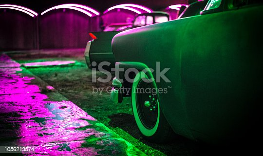 A fender from a 1950's American car, bathed in green and pink neon light.