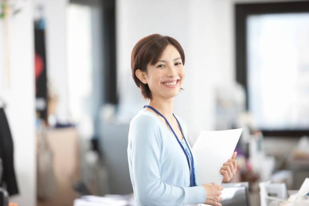オフィスで資料を抱えるol - 女性会社員 ストックフォトと画像