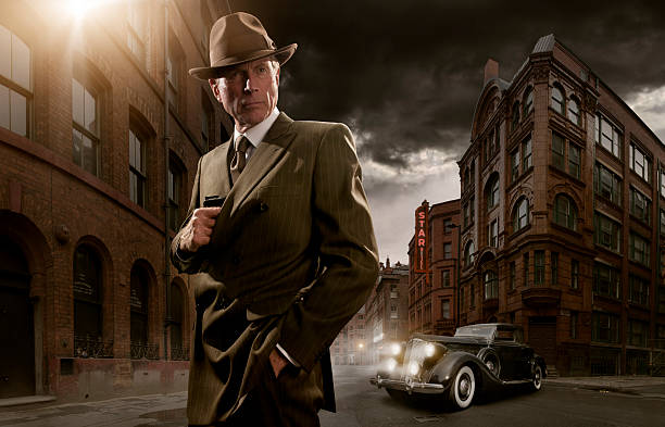 1940's noir gangster 1940's stylised image of man in suit and fedora hat standing in run down city with vintage car in background about to take out gun from pocket gangster stock pictures, royalty-free photos & images